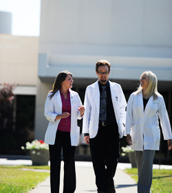 3 clinicians walking outside NUHS Whole Health Center Lombard