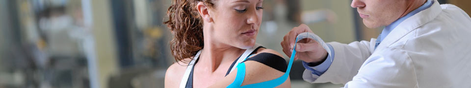 specialist performing kinesiology taping on patient